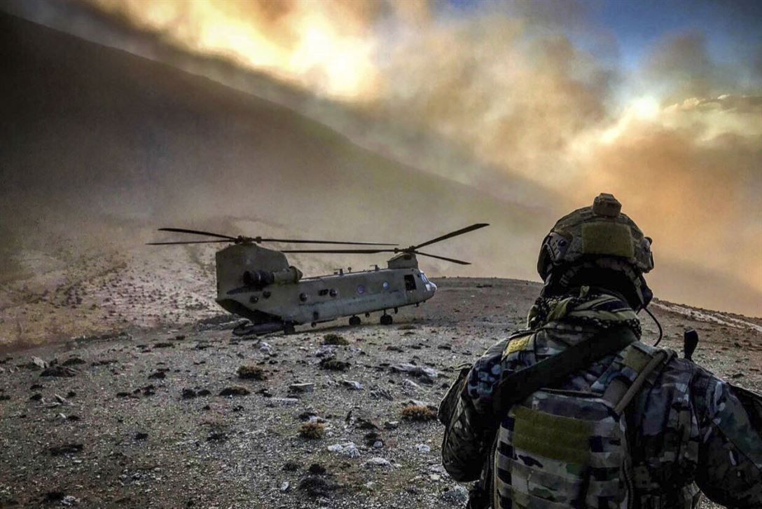 A soldier in fatigues looks at a helicopter on the dusty side of a mountain