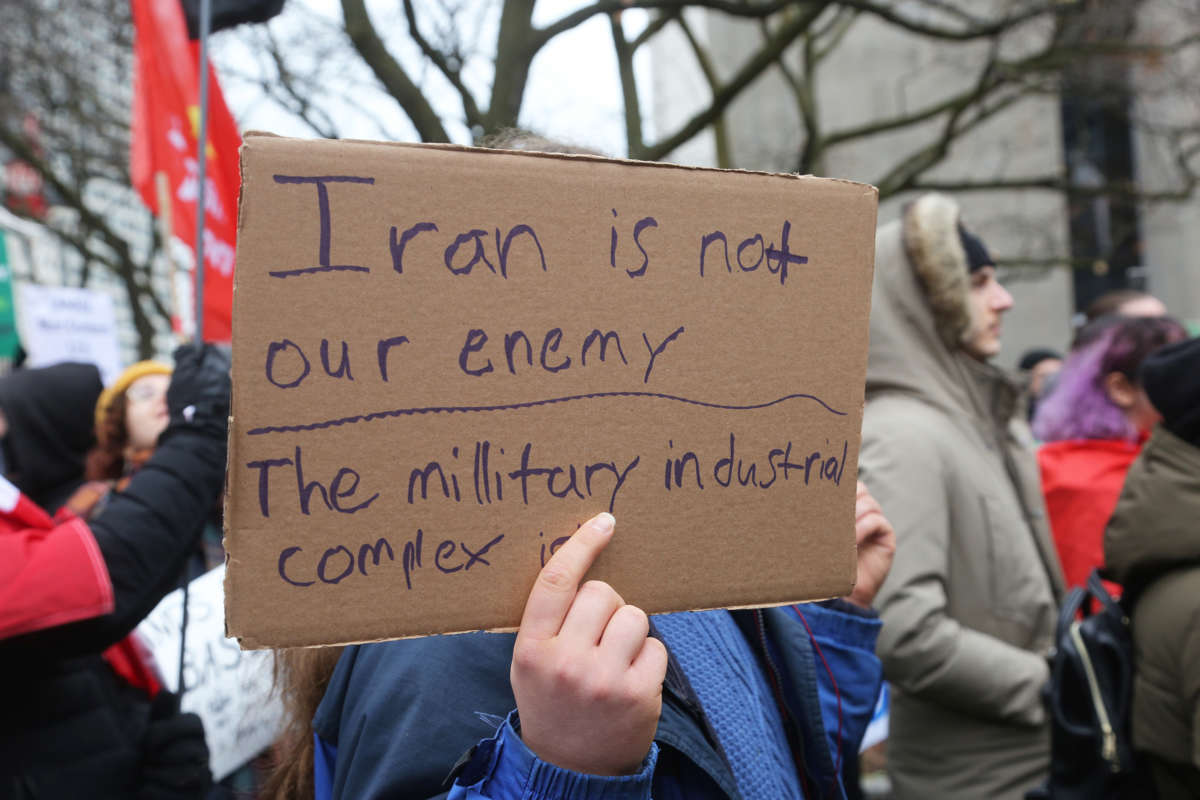 "A protester holds a sign reading ""IRAN IS NOT OUR ENEMY, THE MILITARY INDUSTRIAL COMPLEX IS"""