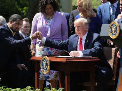 President Trump shakes hands with Pastor Darrell Scott before signing an executive order during an event in the Rose Garden, May 3, 2018, in Washington, D.C. A group run by Scott gave away $25,000 in cash-stuffed envelopes at events promoting Trump.
