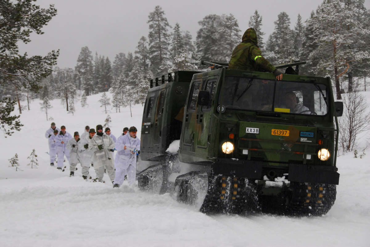 Soldiers dressed in white jog behind a military vehicle driving in the snow