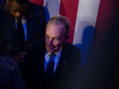 Mike Bloomberg stands in front of a U.S. flag flanked by supporters