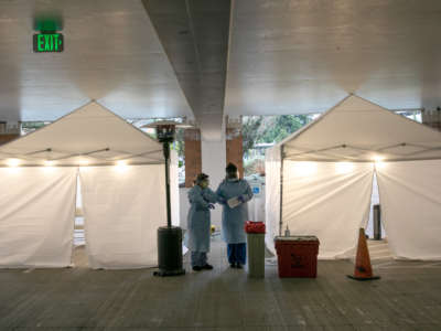 Two medical professionals in scrubs and masks stand between two tents at a drive-through human coronavirus testing station