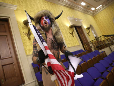 "A man identified as Jacob Anthony Chansley, who also goes by the name ""QAnon Shaman,"" screams ""Freedom"" inside the Senate chamber after the U.S. Capitol was breached by a mob during a joint session of Congress on January 6, 2021, in Washington, D.C."