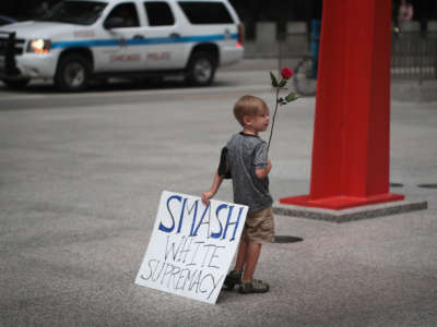 "A young boy holds a sign reading ""SMASH WHITE SUPREMACY"" in one hand and a rose in the other during a protest"