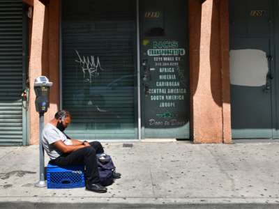 A man sits on a turned-over milk crate in front of shuttered businesses