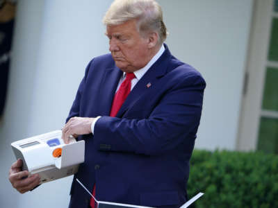 President Trump holds a 5-minute test for COVID-19 from Abbott Laboratories during the daily briefing on the novel coronavirus, COVID-19, in the Rose Garden of the White House in Washington, D.C., on March 30, 2020.