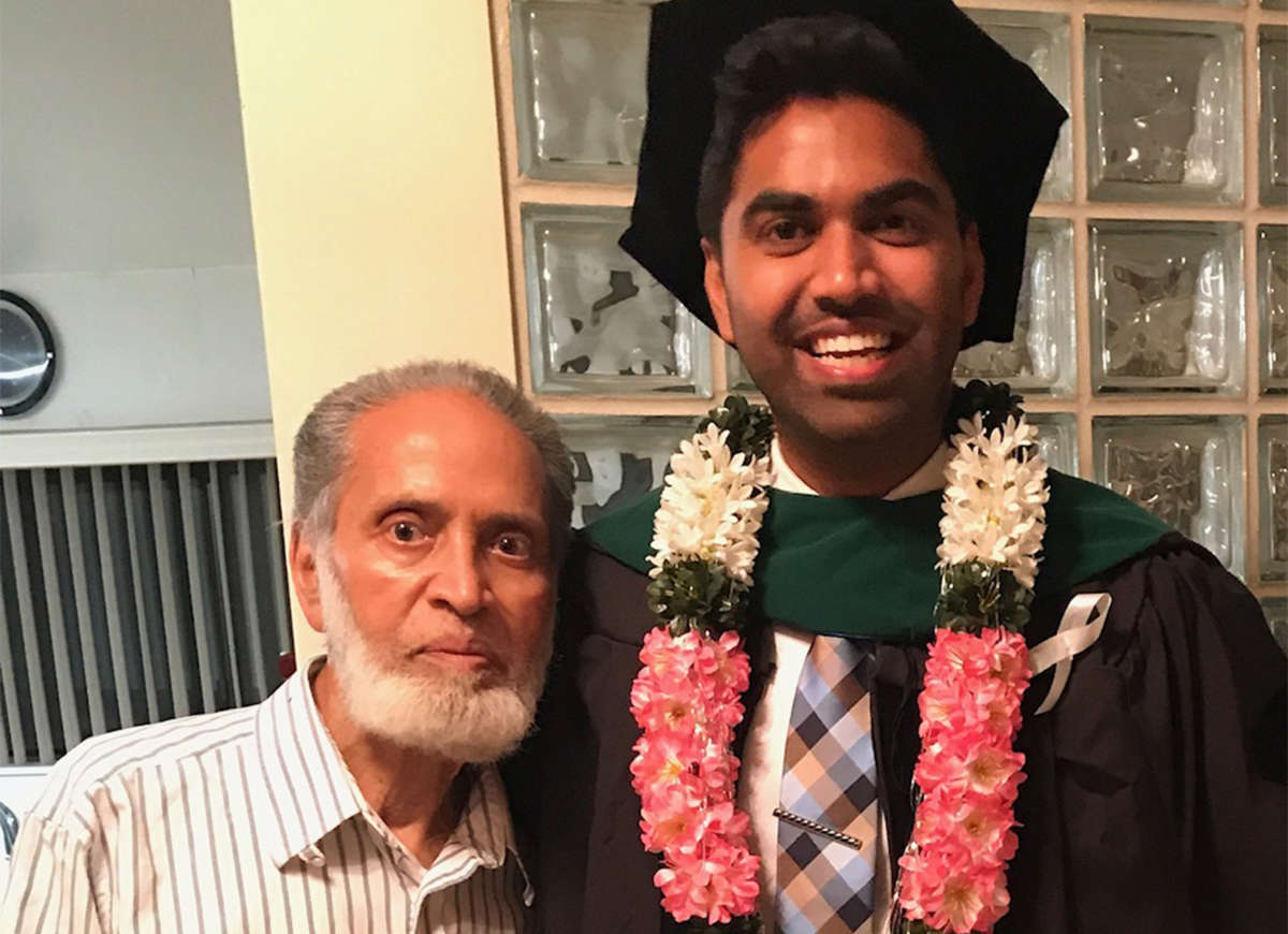 An older man stands beside his grandson, who is dressed for his graduation