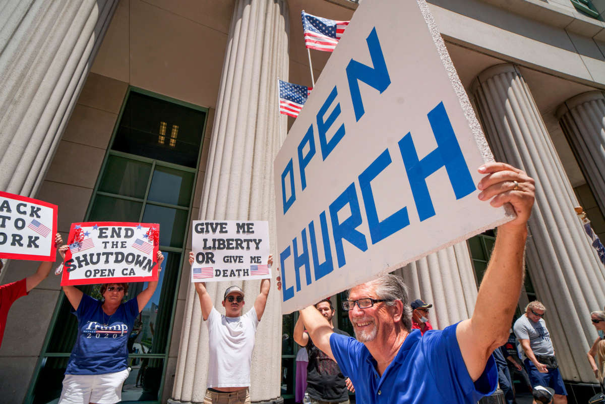 Demonstrators hold signs demanding their church to reopen, protest during a rally to reopen California and against stay-at-home directives on May 1, 2020, in San Diego, California.