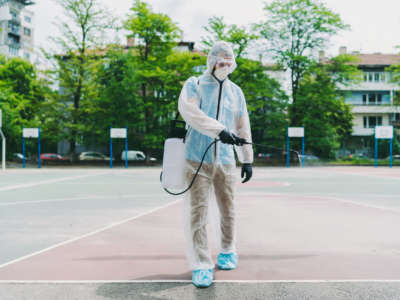 A person disinfects a basketball court.