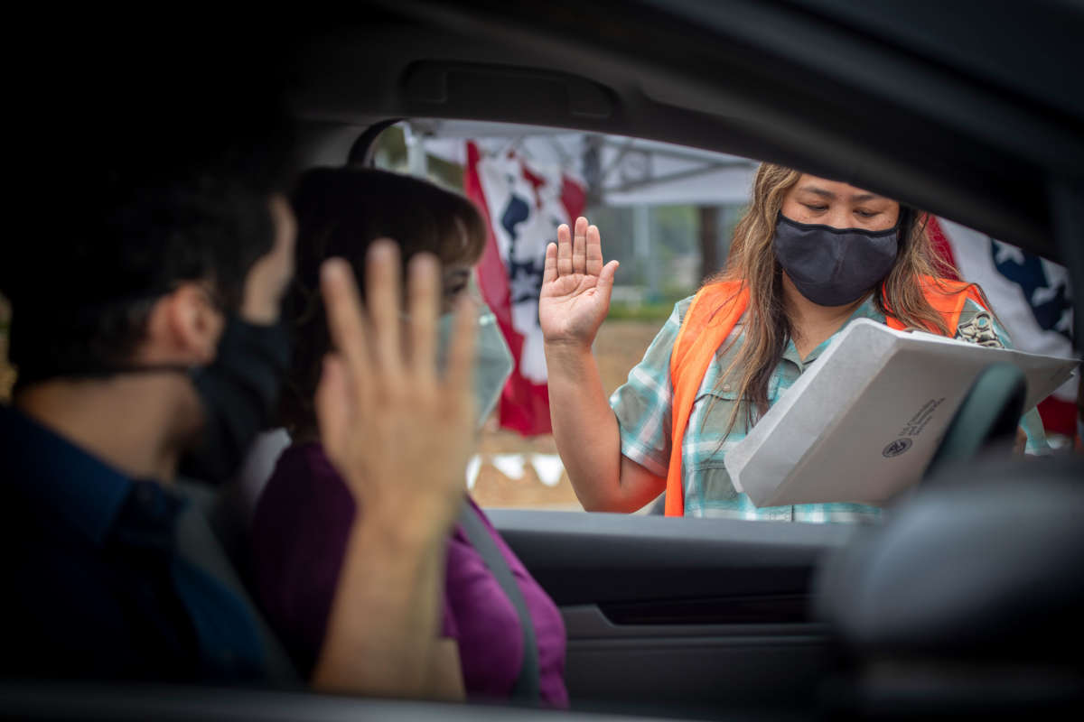U.S. Citizenship and Immigration Services officer Rochelle Reyes, right, administers the oath of allegiance to a mother and son during a drive-through citizenship naturalization at the Chet Holifield Federal Building parking lot, June 23, 2020, in Laguna Niguel.