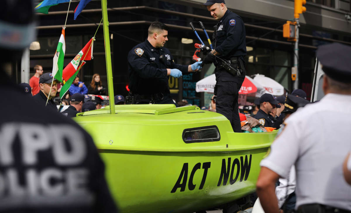 Police gather around a small sailboat that was dropped off in Times Square as part of a protest by the environmental group Extinction Rebellion on October 10, 2019, in New York City.