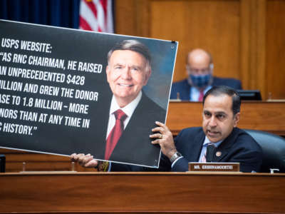 Representative Raja Krishnamoorthi holds a picture referencing Robert Duncan, chairman of the USPS Service Board of Governors, during a hearing before the House Oversight and Reform Committee on August 24, 2020, on Capitol Hill in Washington, D.C.