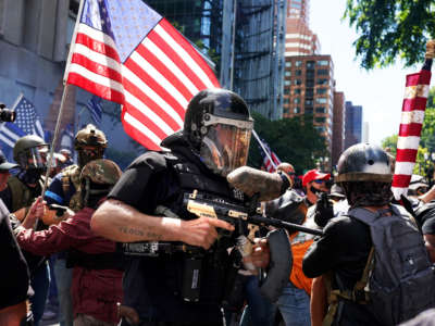 A member of the Proud Boys fires a paint ball gun into a crowd of anti-police protesters on August 22, 2020, in Portland, Oregon.
