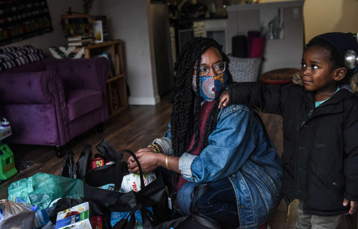 After checking the food and essential items that were delivered to her, Sevonna Brown of Black Women's Blueprint looks at her son on May 11, 2020, in the Bedford-Stuyvesant neighborhood in the Brooklyn borough in New York City.
