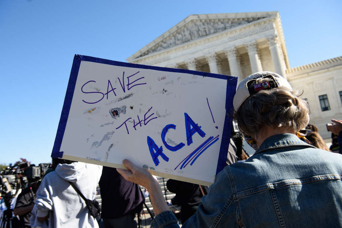 A demonstrator holds a sign in front of the Supreme Court in Washington, D.C., on November 10, 2020.
