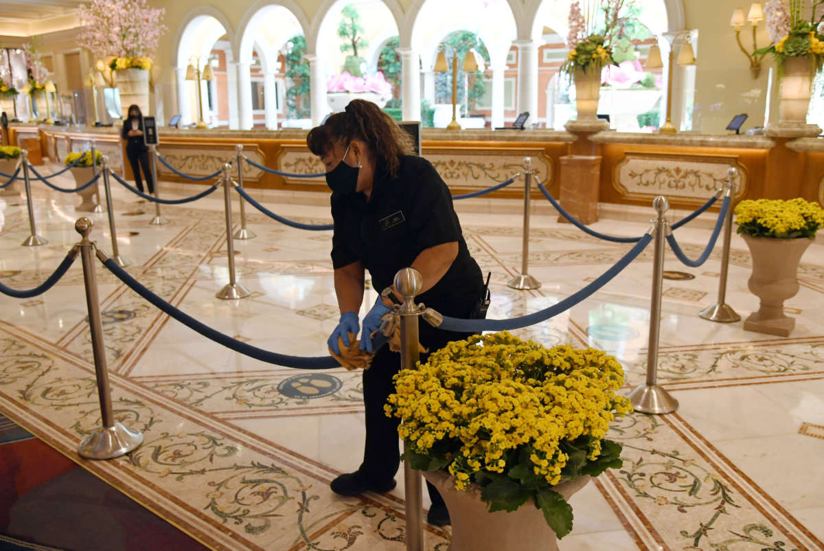 A worker cleans stanchions and ropes in the front desk area of Bellagio Resort & Casino on the Las Vegas Strip on June 4, 2020, in Las Vegas, Nevada.