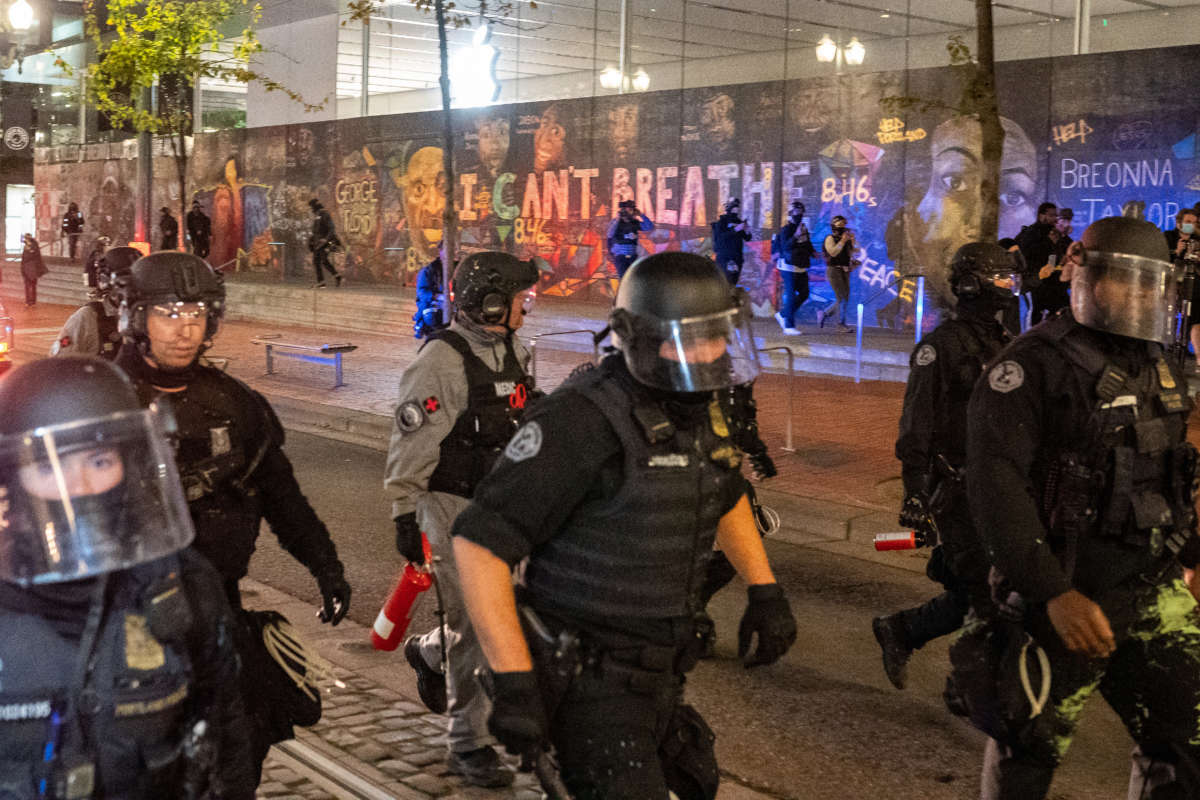Portland police disperse a crowd of protesters past a mural of George Floyd and Breonna Taylor on September 26, 2020, in Portland, Oregon.