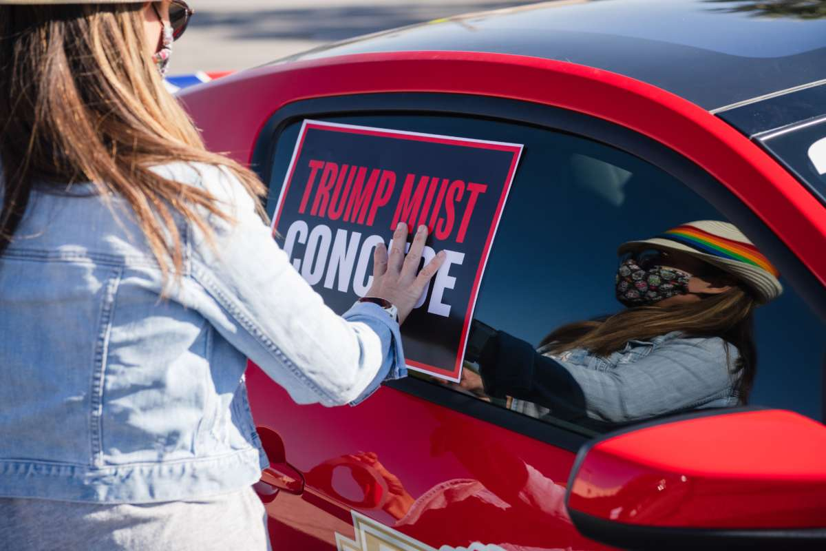 "A woman tapes a ""TRUMP MUST CONCEDE"" sign to the side of her car"
