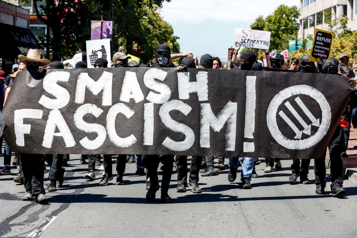 "Antifa members march down a street behind a banner reading ""SMASH FASCISM"""
