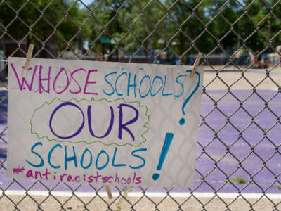 A child's sign hangs on a school fence during a Day of Solidarity for Antiracist Schools in Madison, Wisconsin.