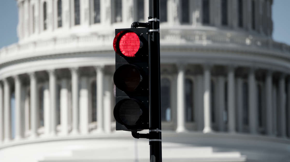 A red stoplight in front of the U.S. Capitol Building.