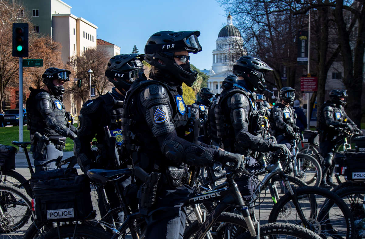 Sacramento Police officers in riot gear on bikes stay close to Antifa protesters marching near the California State Capitol on January 20, 2021, in Sacramento, California.