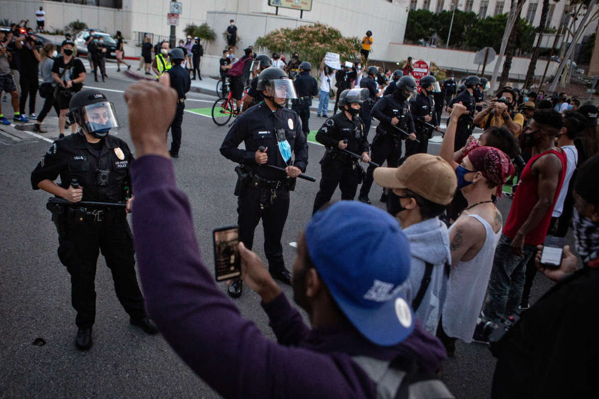 Black Lives Matters protesters stand united as they confront LAPD, protesting the killing of George Floyd in Minnesota by police on May 27, 2020, in Los Angeles, California.