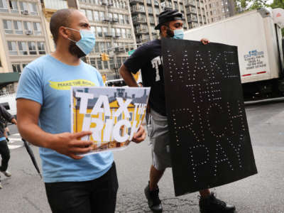 "A protester holds a lit sign reading ""MAKE THE RICH PAY"""