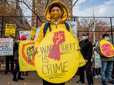 "A protester holds a sign reading ""WAGE THEFT IS A CRIME"""