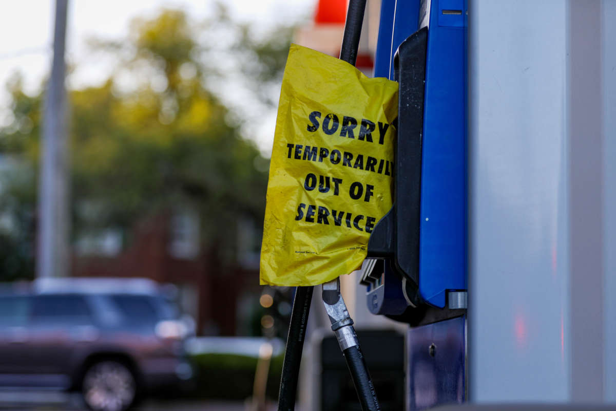 """A yellow bag reading """"SORRY; TEMPORARILY OUT OF SERVICE"""" covers a gas pump"""