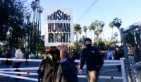 Social activists, including a coalition of homeless-serving organizations, homeless residents and supporters rally at the start of a 24-hour vigil to block a planned shutdown of a homeless encampment at Echo Park Lake in Los Angeles, California, on March 24, 2021.