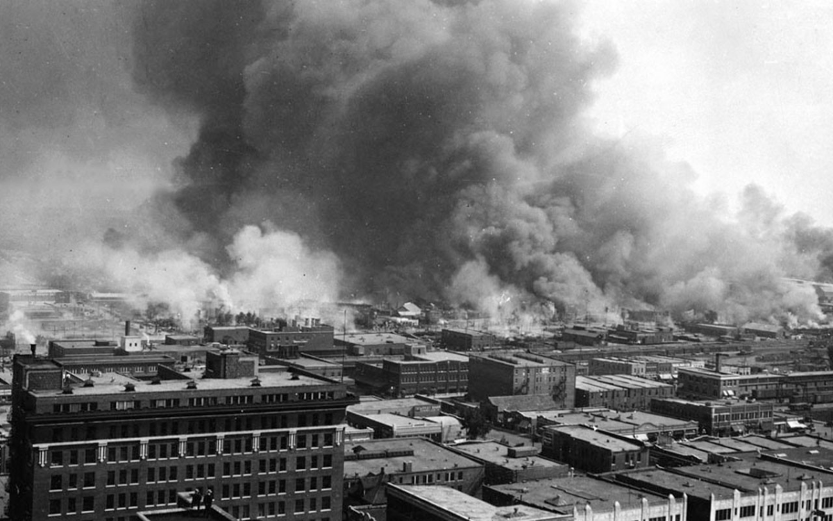 an aerial view of the Tulsa Race Riot with smoke billowing up from buildings