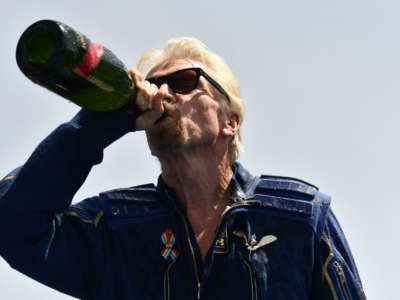 Virgin Galactic founder Sir Richard Branson drinks champagne with crew members after flying into space aboard a Virgin Galactic vessel, near Truth and Consequences, New Mexico, on July 11, 2021.