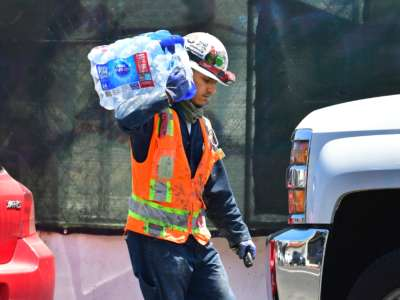 A construction worker carries a 24-pack of bottled water over his shoulder on June 14, 2021 in Los Angeles, where an early season heat wave was in full swing across much of California.