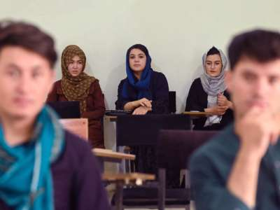 Women in Hijab sit at the back of a classroom