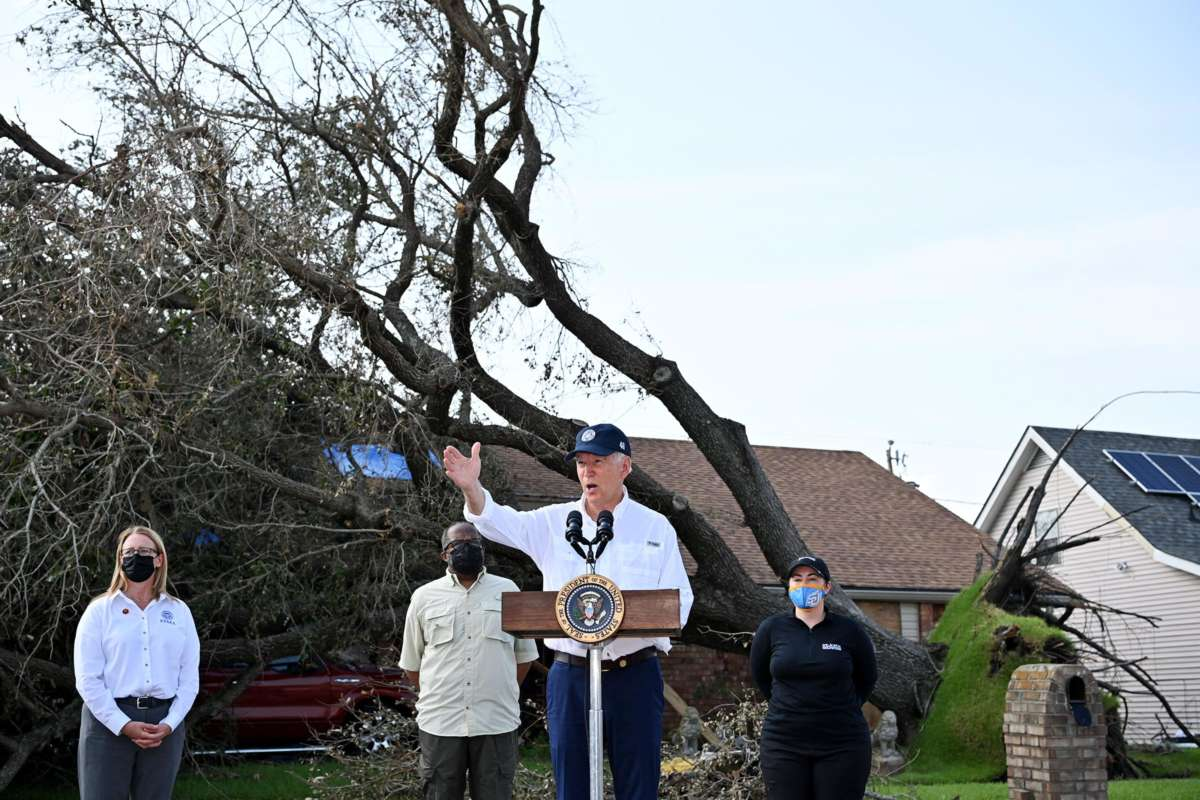 Joe Biden speaks in front of a home with a downed tree laying across its roof