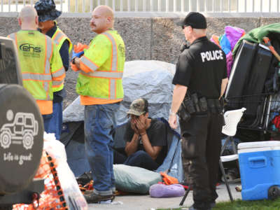 People are evicted from a camp site by Civic Center Park in Denver, Colorado, on September 15, 2021.