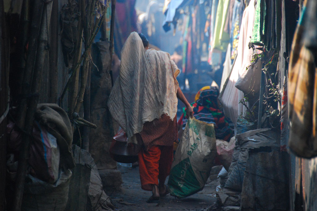 A heavily-laden woman carries water from a communal tap down a cramped side street in the Kallyanpur slum in Dhaka, Bangladesh.