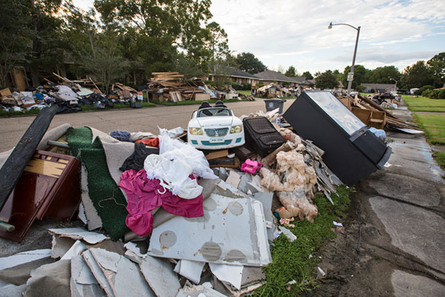 Many residents are still waiting for the piles of debris in front of their homes to be removed after the August flood, as seen along this street in the Monticello neighborhood of Baton Rouge, Louisiana, on September 15. (Photo: Julie Dermansky)