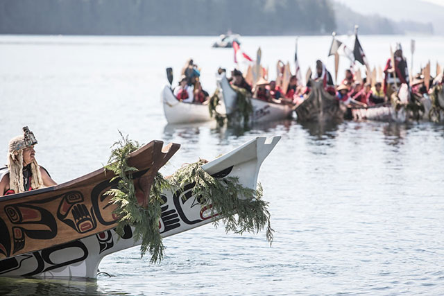 Traditional canoes arrive at Point Grenville, near Taholah, as part of an annual inter-tribal festival celebrating Native history, culture, and tradition. For many tribes, losing home can also mean losing touch with vital cultural and spiritual practices. (Photo: Kris Krüg)