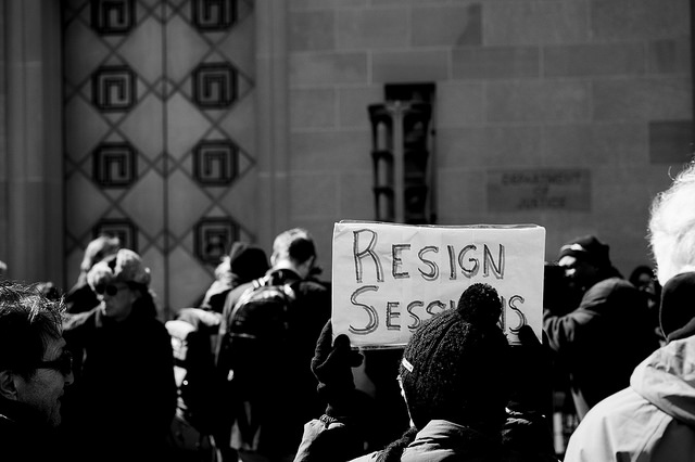 An activist holds a sign at a protest outside of the Department of Justice in Washington, DC, March 2, 2017. (Photo:  Mike Maguire)