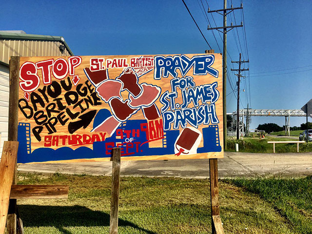 A wooden signs announces a prayer service against the Bayou Bridge Pipeline at St. Paul Baptist Church in rural St. James Parish, Louisiana, where local pastors say,