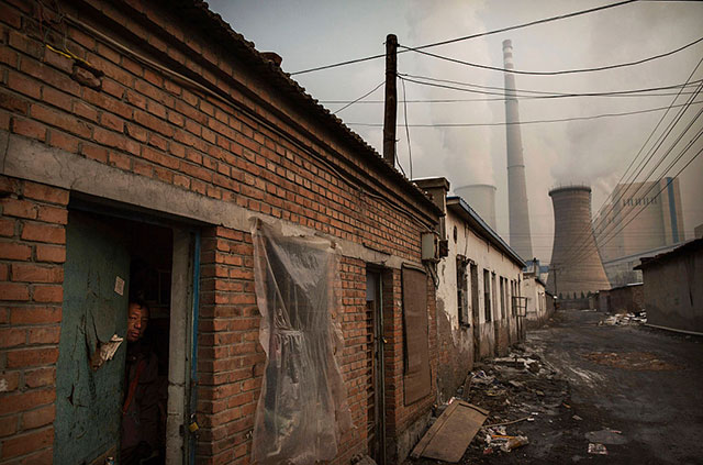 A Chinese migrant worker looks out from the door of his house next to a coal fired power plant on November 27, 2015 on the outskirts of Beijing, China. (Photo: Kevin Frayer / Getty Images)